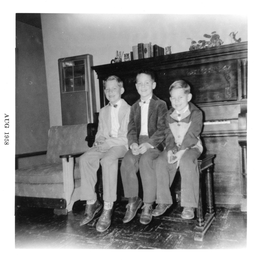 Three boys sitting on a piano bench, black white